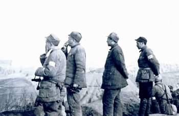 1947年3月,习仲勋(左三)与彭德怀等在陕北青化砭战场前线阵地上。