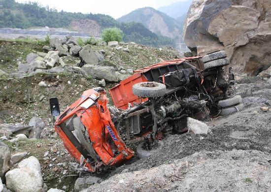 汽车被山体滑坡的山石砸出公路