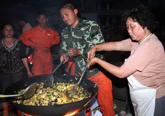 5月16日,一位群众正在为搜救官兵炒菜